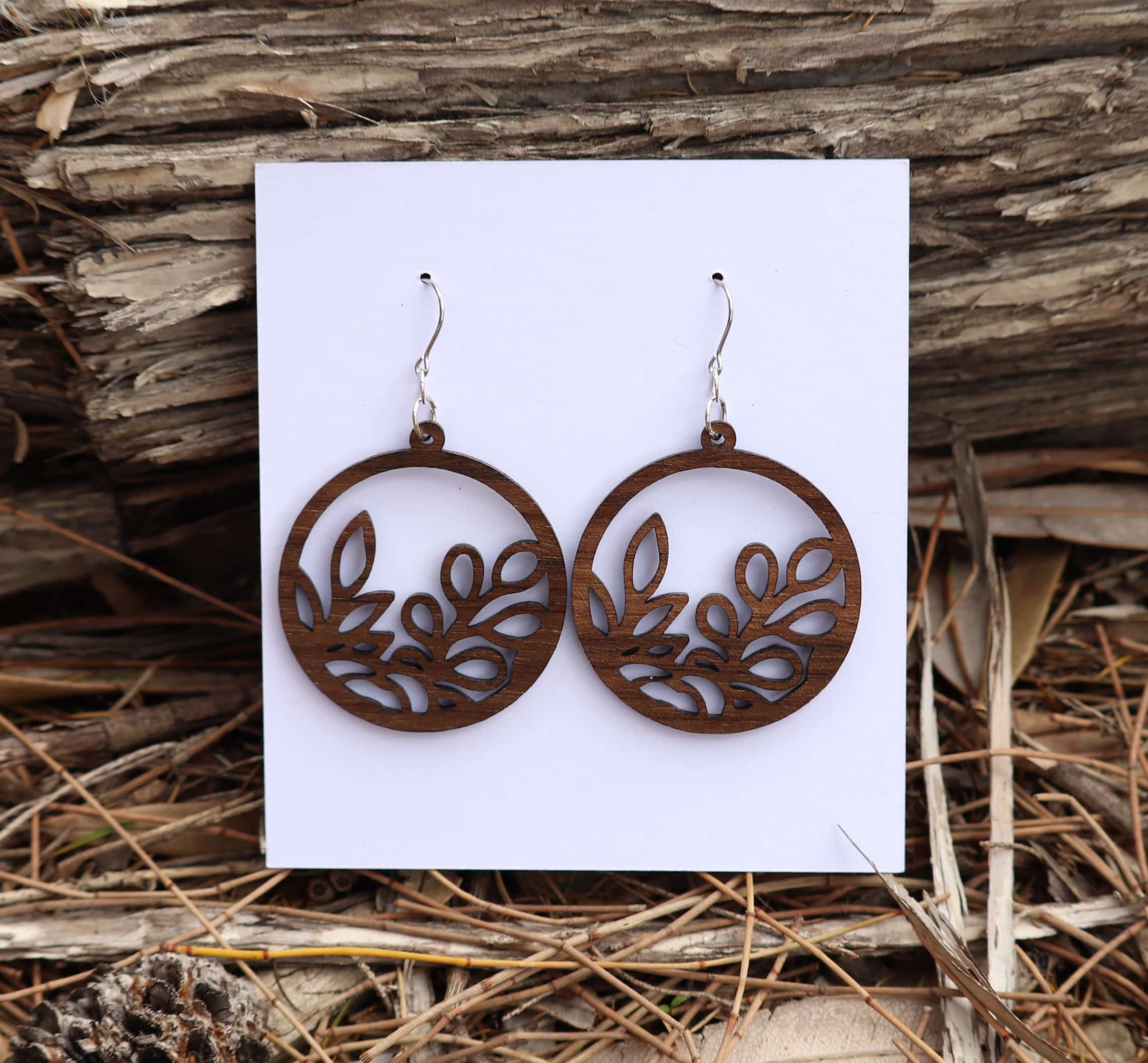 Round wooden queensland walnut earrings with intricate leaf pattern.