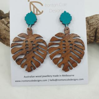 Monstera leaf earrings made from queensland walnut and paired with an aqua blue post.